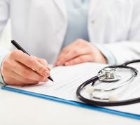 Eine Hand macht Notizen, ein Stethoskop liegt daneben