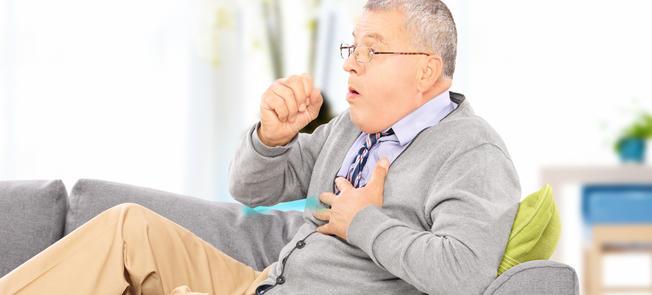älterer Mann auf der Couch hustet
