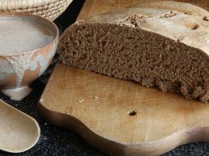Schüssel mit Sauerteig, angeschnittenes Brot