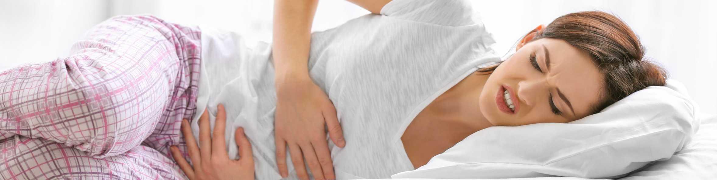 Frau liegt mit unklaren Schmerzen im Bett