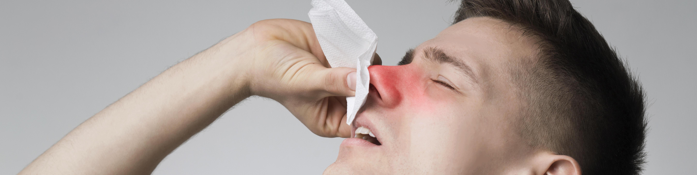 junger Mann, Schnupfen, putzt sich die Nase