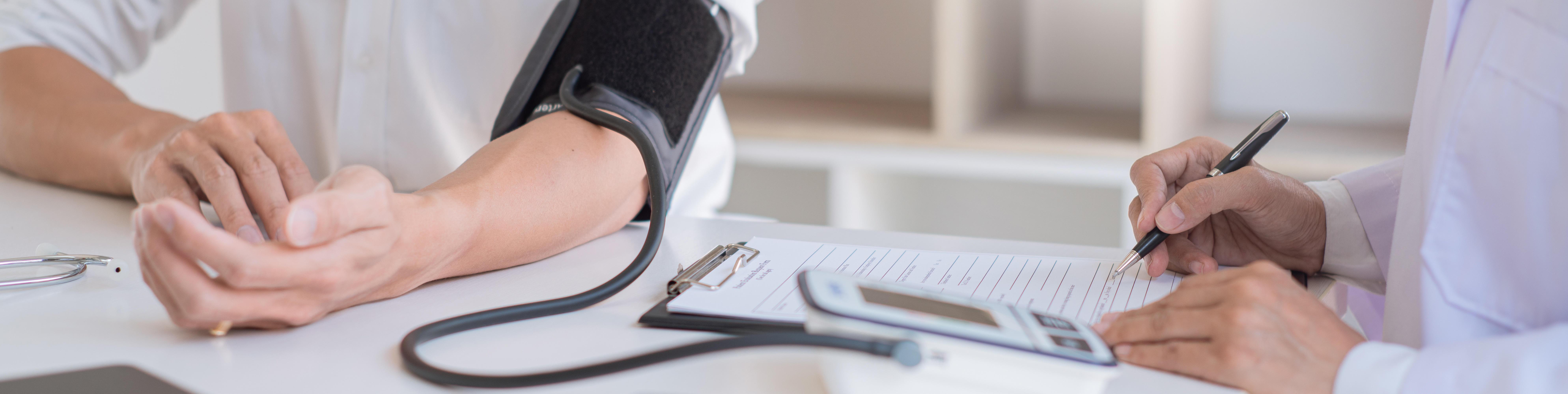 Arzt misst Blutdruck beim Patienten und trägt Wert in Tabelle ein