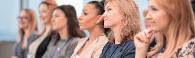 Frauen sitzen in einer Reihe und hören aufmerksam zu