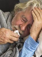 Alter Mann liegt im Bett und hustet
