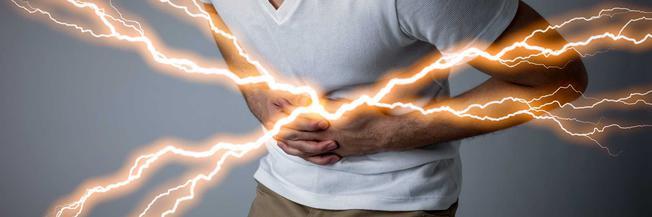 Mann hält sich den Bauch, aus dem Blitze kommen