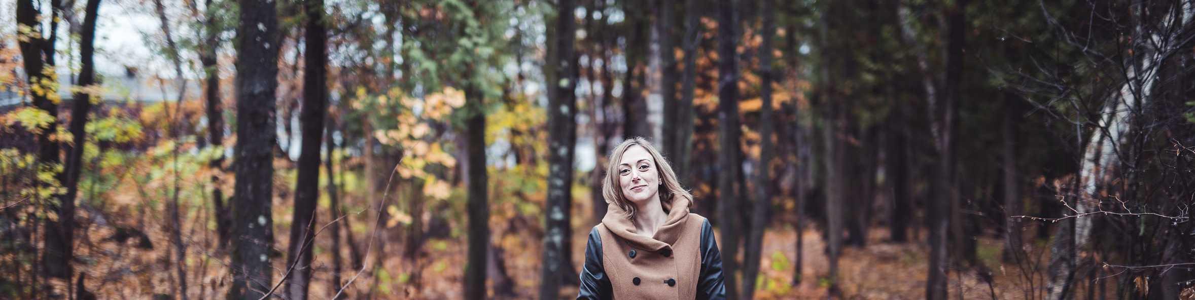 Frau steht im Herbstwald-Lichtmangel