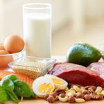 Lebensmittel wie Eier, Fleisch, Kartoffeln und Brokkoli auf einem Holzbrettchen