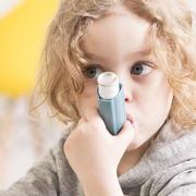 Kind mit Asthma-Spray im Mund
