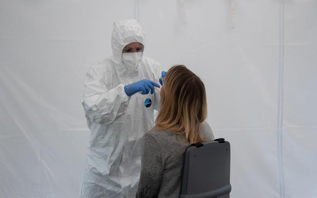 MFA im Schutzanzug nimmt Coronavirus-Abstrich