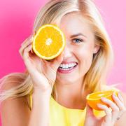 junge Frau hält sich Orangenscheibe vors Auge